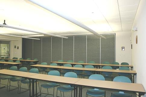 Chairs in front of long tables in the conference room.